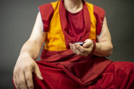 Photo for Buddhist monk holding a candle with a candlestick in his hand - Royalty Free Image