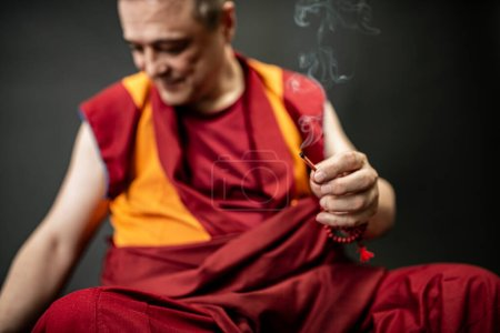 Photo for Buddhist monk holds a candle and lights an incense stick - Royalty Free Image