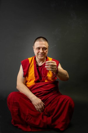Photo for Buddhist monk holding a smoking incense stick in his hand - Royalty Free Image