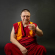 Buddhist monk holding a smoking incense stick in h...