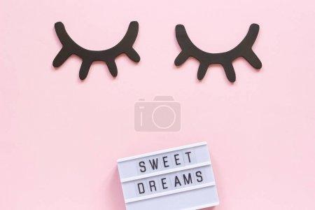 Photo pour Texte Lightbox Doux rêves et cils noirs décoratifs en bois, yeux fermés sur fond de papier rose. Concept Bonne nuit Carte de voeux Vue du dessus Pose créative à plat . - image libre de droit