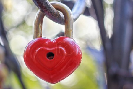 Red lock in the form of a heart hangs on an iron rail.