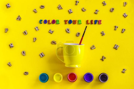 Text Color your life from colorful letters, gouache, yellow coffee cup with paintbrush, scattered wooden letters on yellow background  Flat lay Top view,  greeting card. Concept - Paint your life.