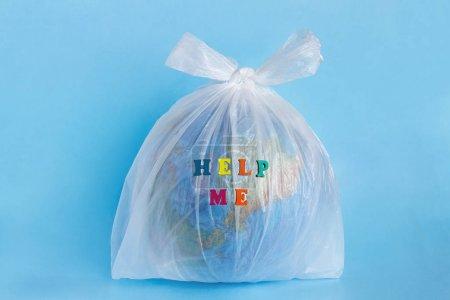 Photo pour Texte Help me and Model planet Earth in polyethylene plastic jetable package on blue background. Problèmes écologiques La pollution de l'environnement par les déchets plastiques en polyéthylène Journée mondiale de la Terre - image libre de droit
