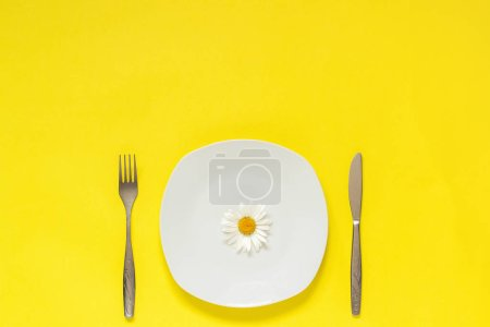 Photo for One flower chamomile daisy on plate, cutlery fork knife on yellow paper background Concept vegetarian, healthy eating, diet or anorexia Creative top view Copy space template for lettering text or design. - Royalty Free Image