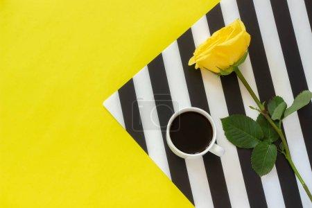 Photo pour Tasse de café et rose jaune sur une élégante serviette noire et blanche sur fond jaune - image libre de droit