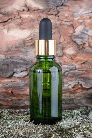 Photo pour Flacons cosmétiques en verre vert avec sérum, huile essentielle sur mousse verte et écorce d'arbre. Natural Organic Spa Concept cosmétique Vue de face. - image libre de droit