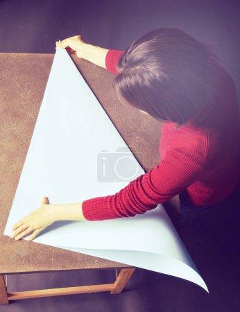 Real woman folding light blue sheet of paper