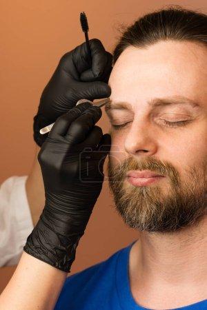 Photo pour Barbier professionnel faisant la procédure de filetage et de corriger la forme des sourcils pour jeune client masculin avec une pince à épiler dans le salon de coiffure. Barbier au travail. Concept de soin des sourcils. Cueillette des sourcils - image libre de droit