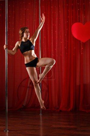 Photo pour Sexy pole dancer se produit sur un pylône. Elle a sauté. Flexibilité, plasticité et force. - image libre de droit