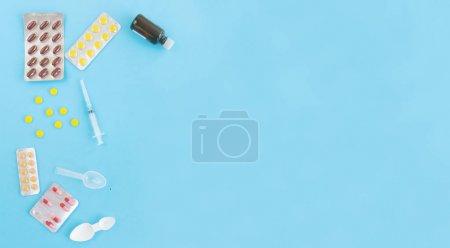 Photo pour Seringue et pilules médicinales, capsules sur fond bleu.Concept de médicine.Médicaments pour le traitement des maladies, virus, saison froide automnale, béribérie, hypothermie, vaccination. Espace de copie - image libre de droit
