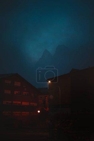Silueta de una gran montaña detrás de un par de edificios en una ciudad espeluznante