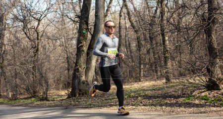 Photo for ALMATY KAZAKHSTAN - MARCH 16 2019: An unidentified man runs through a grove during the spring marathon in the city of Almaty, in a grove named after Baum on March 16 - Royalty Free Image