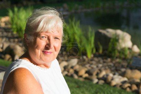 Photo pour Femme mûre avec les cheveux gris et la bouche fermée sourire en regardant la caméra avec un peu d'espace de copie - image libre de droit