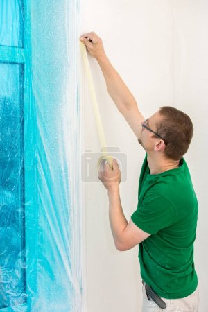 Man protecting window with plastic foil and tape before painting.