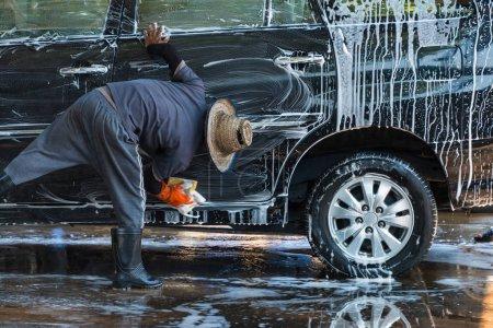 Photo pour Homme travailleur nettoyage automobile avec éponge sur une station de lavage de voiture - image libre de droit