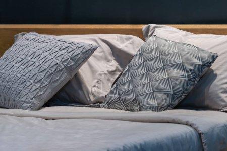 Photo pour Oreillers en tissu gris moderne et motif à carreaux sur la décoration intérieure du lit - image libre de droit