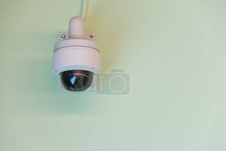 Photo for Modern CCTV camera on the green wall concept or surveillance and monitoring with blue sky background - Royalty Free Image