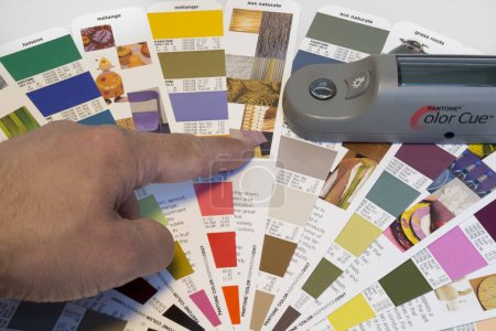 Photo for ZAGREB. CROATIA - OCTOBER 20, 2014: Hand pointing at color sample on pantone catalog in printing house. Pantone is reference catalog for mixing colors - Royalty Free Image