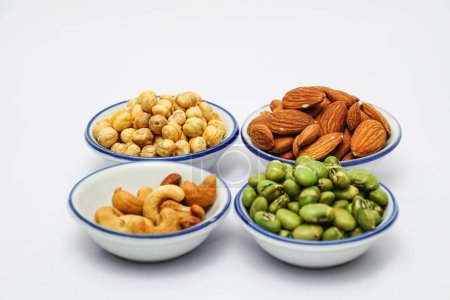 Photo for Collection of organic cashew nuts, almonds, hazelnuts and green beans in bowls on white background - Royalty Free Image