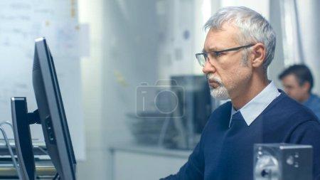 Photo pour Plan rapproché d'un ingénieur en chef travaillant à son bureau, quelques éléments techniques reposant sur son bureau. Son assistant travaille à son bureau en arrière-plan . - image libre de droit