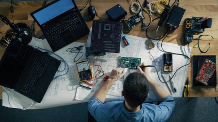 Photo for Top View of Young IT Technician Soldering Circuit Board. His Table is Full With Various Computer Parts, Motherboards, Laptops, Cables. Morning Sun Illuminates His Desk. - Royalty Free Image