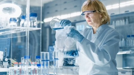 Senior Female Chemist in Safety Glasses Mixes Smoking Liquids in a Beakers. She Works in a Bright Modern Laboratory with Shelves full of Samples, Test Tubes and Advanced Technological Equipment.
