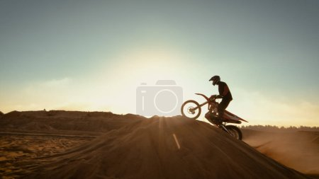 Photo for Professional Motocross Motorcycle Rider Jumping Over the Dune and Further Down the Off-Road Track. Shot on Deserted Quarry while Sun is Setting. - Royalty Free Image