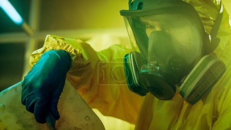 In the Underground Drug Laboratory Clandestine Chemist Wearing Protective Mask and Coverall Mixes Chemicals. He Pours Liquid From Canister into Bowl to Make New Batch of Synthetic Narcotics. He Squats in the Abandoned Building.