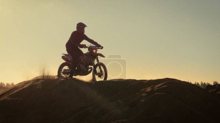 Professional Motocross Motorcycle Rider Drives Over the Dune and Further Down the Off-Road Track. It's Sunset.