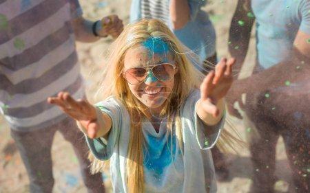 Photo pour High Angle Shot of a Blonde Girl Jetant de la poudre colorée dans la foule au milieu des célébrations du festival hindou Holi. Ils s'amusent énormément en cette journée ensoleillée . - image libre de droit