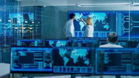 Photo pour Dans la salle de surveillance du système, deux opérateurs principaux travaillent sur une grande carte interactive. L'installation est pleine d'écrans affichant des données techniques . - image libre de droit