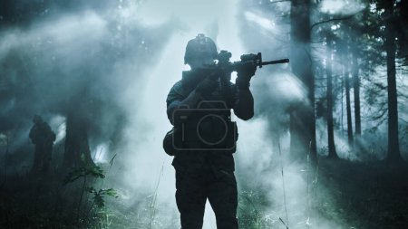 Silhouette of the Fully Equipped Soldier Moving Through Smokey Forest with Rifle Ready To Shoot. Reconnaissance Military Operation. Squad Moving Behind Him. Dark and Cold Ambient.