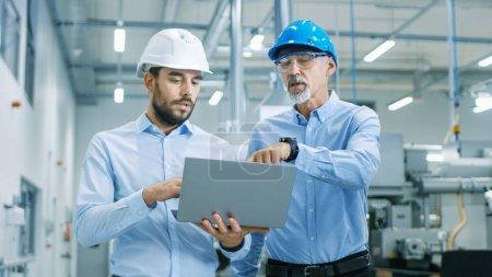 Photo pour Chef du projet détient portable et discute des détails de produit avec l'ingénieur en chef tandis qu'ils marcher à travers l'usine moderne. - image libre de droit