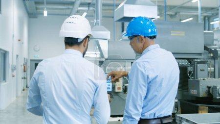 Photo pour Vue arrière de la tête du projet détient portable et discuter des détails de produit avec l'ingénieur en chef tandis qu'ils marcher à travers l'usine moderne. - image libre de droit