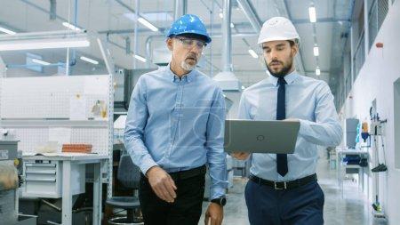 Photo pour Chef du département détient portable et discuter des détails du produit avec l'ingénieur en chef tandis qu'ils marcher à travers l'usine moderne. - image libre de droit