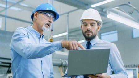Photo pour Chef du département contient ordinateur portable et discute des détails du produit avec l'ingénieur en chef. Ils porter casque et travail à l'usine moderne. - image libre de droit