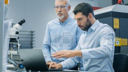 Photo pour Deux scientifiques industrielles / ingénieurs / techniciens ont Discussion tout en travaillant sur ordinateur portable. Dans le laboratoire moderne de fond / matériel d'usine. - image libre de droit