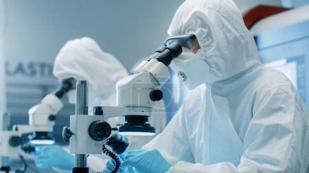 Two Engineers/ Scientists/ Technicians in Sterile Cleanroom Suits  Control Manufacturing Machinery Work and Use Microscopes for Component Adjustment and Research. They Work in an Electronic Components Manufacturing Factory.