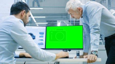 Photo pour Designer industriel a une conversation avec l'ingénieur principal tout en travaillant dans le programme de CAO, On a un écran vert Chroma Key Template Idéal pour Mockup. Il travaille sur un ordinateur personnel avec deux moniteurs . - image libre de droit