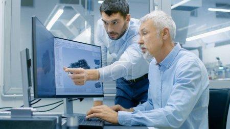 Photo pour Designer industriel a Conversation avec ingénieur principal tout en travaillant au programme de CAO, conception nouveau composant. Il travaille sur ordinateur personnel avec deux moniteurs. - image libre de droit
