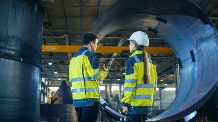 Photo pour Mâle ouvrier industriel et ingénieur en chef de la femme dans un casque discutent de nouveau projet de l'usine de métallurgie. Ils se tiennent au milieu de l'installation de l'industrie lourde. - image libre de droit