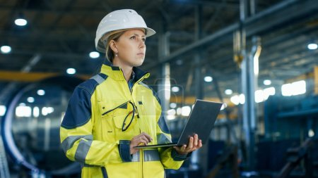 Photo for Female Industrial Engineer in the Hard Hat Uses Laptop Computer while Standing in the Heavy Industry Manufacturing Factory. In the Background Various Metalwork Project Parts Lying - Royalty Free Image