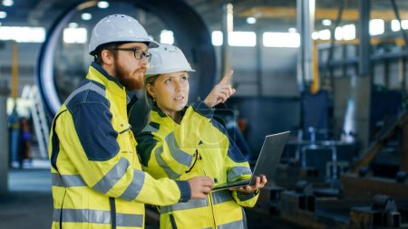 Portrait of Male and Female Industrial Engineers in Hard Hats Discuss New Project while Using Laptop. They Wear Safety Jackets.They Work at the Heavy Industry Manufacturing Factory.