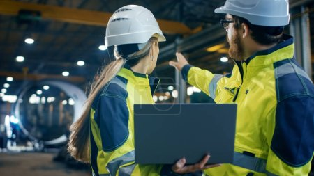 Photo for Inside the Heavy Industrial Factory Female Industrial Engineer Holds Laptop and Has Discussion with Project Manager. They Wear Hard Hats and Safety Jackets. In the Background Welding/ Metalwork in Progress. - Royalty Free Image
