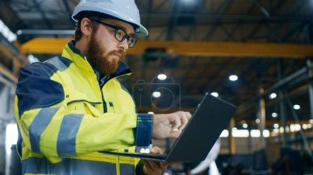 Photo pour Ingénieur industriel en Hard Hat port de veste de sécurité utilise ordinateur portable à écran tactile. Il travaille à l'usine de fabrication de l'industrie lourde. En arrière-plan Les processus de soudage / travail des métaux sont en cours . - image libre de droit