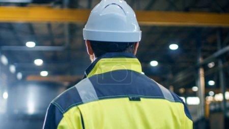 Photo pour Ingénieur industriel dans Hard Hat et la veste de sécurité regarde autour dans la grande usine de fabrication de l'industrie lourde . - image libre de droit