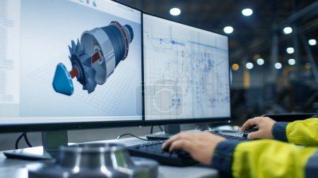 Photo pour À l'intérieur de l'usine de l'industrie lourde Gros plan des mains de l'ingénieur industriel travaillant sur l'ordinateur personnel avec deux moniteurs Conception de turbine / moteur en 3D, à l'aide du programme CAO . - image libre de droit