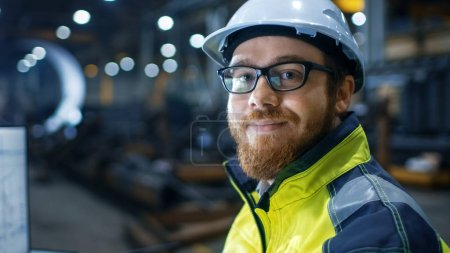 Industrial Engineer Wearing Hard Hat,  Safety Jacket and Glasses Smiles on Camera. He Works in Big Heavy Industry Factory.
