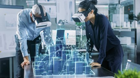Photo for Male and Female Architects Wearing  Augmented Reality Headsets Work with 3D City Model. High Tech Office Professional People Use Virtual Reality Modeling Software Application. - Royalty Free Image